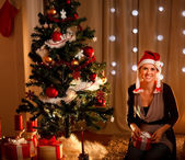 Portrait of beautiful young woman near Christmas tree holding gi — Стоковое фото