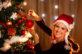 Beautiful woman hanging toy on Christmas tree — Stock Photo