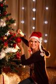 Mujer hermosa colgante bola de navidad árbol de navidad — Foto de Stock