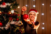 Pretty female near Christmas tree showing Christmas toy — ストック写真
