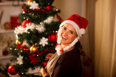 Smiling young woman decorating Christmas tree — Stock Photo