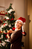 Happy girl decorating Christmas tree — Foto Stock