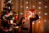 Happy girl in Santa hat near Christmas tree with present box — ストック写真