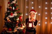 Beautiful girl near Christmas tree presenting gift box — Stock Photo