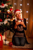 Happy young woman near Christmas tree hugging present box — Stock Photo