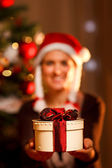 Closeup on hand presenting gift box and smiling woman and Christ — ストック写真