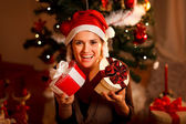Portrait of pretty girl near Christmas tree holding present boxe — Stock Photo