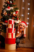 Pretty woman near Christmas tree looking out from pile of presen — Stock Photo