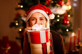 Smiling young woman near Christmas tree — Stock Photo