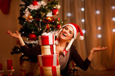 Happy female near Christmas tree with tower of present boxes — Stock Photo