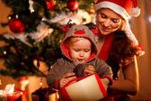 Młoda matka pomaga zainteresowanym dziecko otwarte pudełko w christm — Zdjęcie stockowe