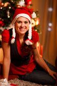 Smiling female sitting near Christmas tree — Stock Photo