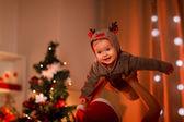 Adorable baby having fun near Christmas tree — Stock Photo
