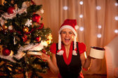 Happy young woman near Christmas with open gift — Stock Photo