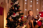 Portrait of lovely baby on mamas hand near Christmas tree — Stock Photo