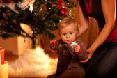 Lovely baby sitting with mama near Christmas tree and looking on — Stock Photo