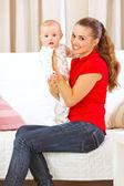Madre feliz sentado en el diván y el bebé adorable celebración en manos — Foto de Stock