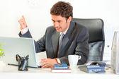 Arg affärsman sitter vid office skrivbord och hotfullt svängde hans fi — Stockfoto