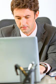 Portrait of modern businessman sitting at office desk and workin — Stock Photo