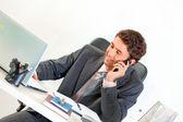 Sitter på kontoret skrivbord leende affärsman talar på mobil och ser — Stockfoto