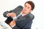 Confident businessman sitting at office desk and putting money in pocket — Stock Photo