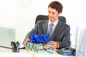 Pleased businessman sitting at office desk and looking on gift — Stock Photo