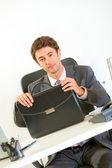Confident businessman sitting at office desk with briefcase — Stock Photo