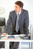 Confident modern businessman holding standing near office desk a — Stock Photo