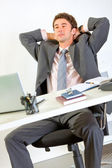 Pleased modern businessman relaxing on office armchair — Stock Photo