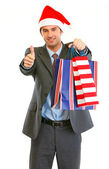 Happy modern businessman in Santa Hat with shopping bags showing — Stock Photo