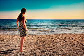 Beautiful woman enjoying sunrise at beach — Stock Photo