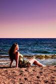 Beautiful woman enjoying sundown at beach — Stock Photo