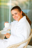 Woman in bathrobe sitting at table on terrace with cup of tea — Stock Photo