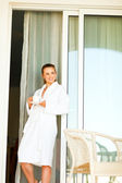 Female in bathrobe standing near big room windows and having cup of coffee — Stock Photo