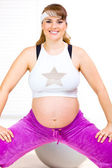 Smiling beautiful pregnant woman making gymnastics at living room — Stock Photo