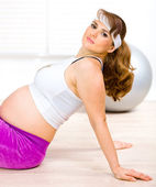 Smiling beautiful pregnant woman sitting on floor and relaxing after exerci — Stock Photo