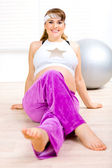 Smiling attractive pregnant woman doing exercise at home — Stok fotoğraf