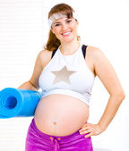 Smiling beautiful pregnant woman in sportswear with exercise mat — Stock fotografie