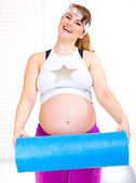 Happy beautiful pregnant woman in sportswear with exercise mat — Stock Photo