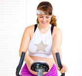 Usmívající se krásná těhotná žena na stacionárním kole — Stock fotografie