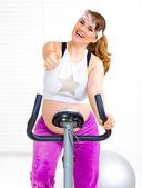 Mulher grávida sentada na bicicleta estática e mostrando os polegares para cima gesto — Fotografia Stock