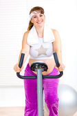 Smiling beautiful pregnant woman working out on static bike — Stok fotoğraf