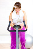 Beautiful pregnant female training on exercise bike — Foto Stock