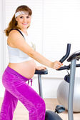 Beautiful pregnant female training on exercise bike — Stock fotografie