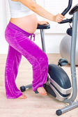 Beautiful pregnant female training on exercise bike — Stok fotoğraf