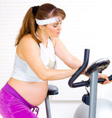 Beautiful pregnant female training on exercise bike — Stock Photo