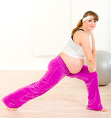 Smiling pretty pregnant woman doing stretching exercises at home — Stock Photo