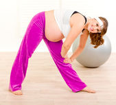 Smiling beautiful pregnant woman doing exercise at living room — 图库照片
