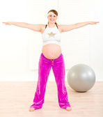 Smiling beautiful pregnant female doing exercise at home — Stock Photo