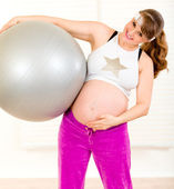 Pregnant female doing pilates exercises on gray ball — Photo